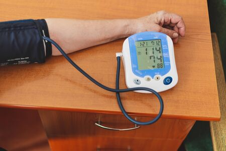 Cardiology device measuring woman's blood pressure - Senior female having her arm stretched for pulse measurement