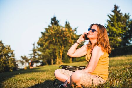 Beautiful woman wearing sunglasses talking on the phone on a sunny day - Casually dressed girl with brown hair chatting on a mobile device while relaxing in nature