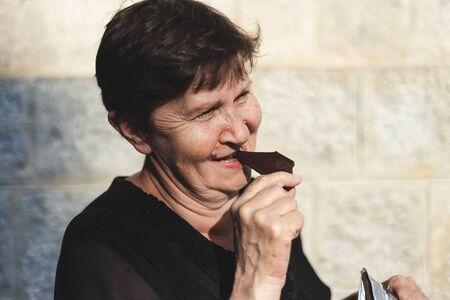 Beautiful senior woman eating chocolate outside - Happy cute old lady feeling good while enjoying sweet candy