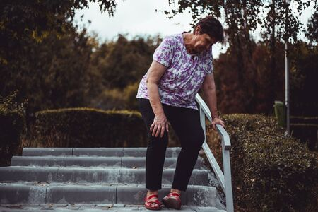 Weak senior woman about to fall while walking down on the stairs outside - Cute old lady slip in the park - Elderly female whit feet pain and muscle discomfort