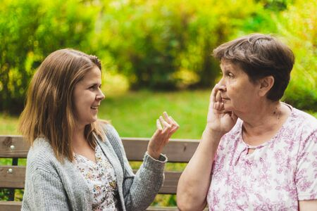 Mother and daughter talking on a bench - Teen giving advice to an adorable old woman - Two women chatting outside
