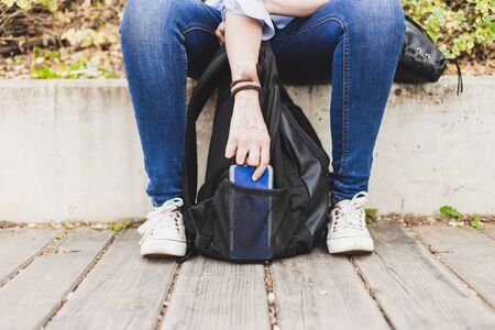 Seated female robber stealing phone out of a backpack's side pocket outside in a campus - Careless student forgotten or lost rucksack stolen by thief