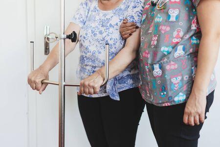 Nurse holding a senior patient that is grabbing a intravenous dropper pole - Saline fluid treatment holder for surgery