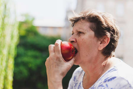 Beautiful portrait of senior woman eating red apple outside on a summer day - Cute old lady with healthy and delicious fruit in nature - Elderly person enjoying nutritious and rich in vitamin snack on a bright sunny day
