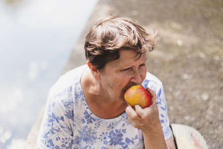 Senior eating apple outside - Portrait of a grandmother sitting and enjoying a nutritious fruit as snack