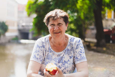 Senior eating apple - Old woman enjoying a fruit while smiling and sitting outside in nature - Healthy vegetarian grandmother having a positive state of mind