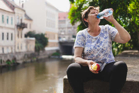 Senior woman drinking from a water bottle for hydration in the heat while sitting in the sun and holding an halved apple