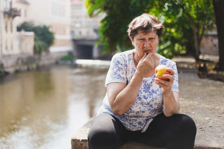 Beautiful senior woman holding red apple outside on a summer day while looking at it with doubt - Cute old lady eating healthy and nutritious fruit in nature - Concept image elderly people with balanced lifestyle Banque d'images