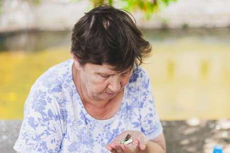 Senior woman holding pills while looking at them outdoors - Cute old lady with brown hair taking vitamins and supplements for a healthy lifestyle - Concept image for addiction