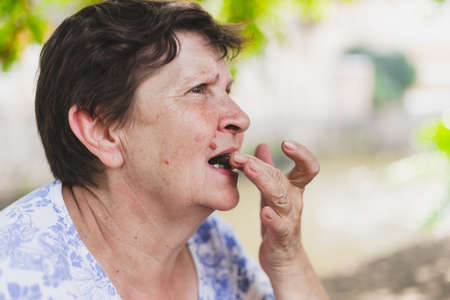 Old woman eating chocolate - Senior preparing biting or putting a piece of sweet snack into her open mouth Foto de archivo