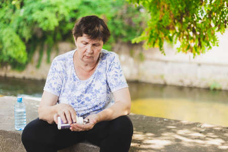 Senior taking medication - Old woman pouring pills from the bottle into her hand while sitting on a concrete edge outside