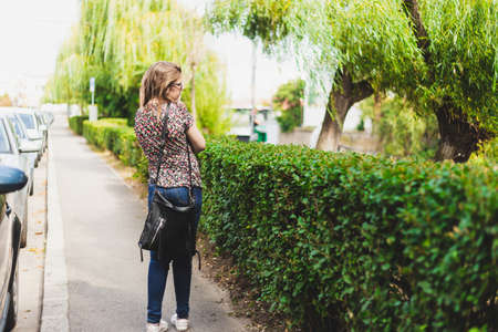 Lonely girl walking on the sidewalk admiring the view - Lonesome lady being lost and terrified outside