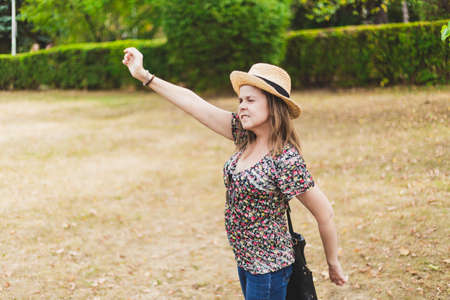 Young woman waving hand - Girl with straw hat and a floral shirt greeting someone that is arriving or leaving