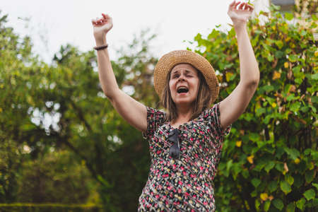 Cute young woman screaming while holding both hands in the air outside - Casually dressed teen girl wearing straw summer hat and floral shirt yelling to someone while lifting arms up in the park