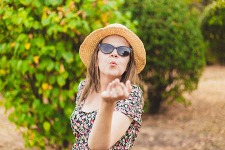 Beautiful happy millennial girl sending air kiss outdoors - Pretty smiling young woman wearing summer straw hat and sunglasses sharing love and affection in the park Foto de archivo