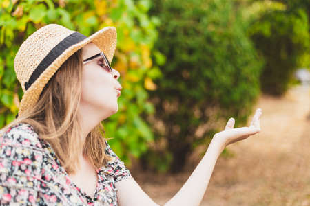 Beautiful young woman blowing air kiss with copy space on a summer day in nature - Hipster girl wearing straw hat and summer glasses sharing love and affection while feeling good in the park on a bright sunny day