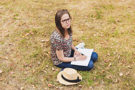 Student studying sitting in university campus while holding notebook on her feet - Education concept image -