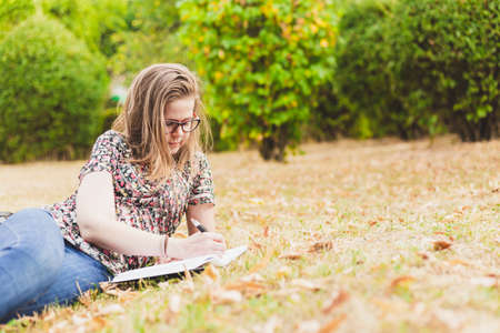 Woman writing outside - Student studying outside in college campus laying on the side in grass while wearing eyeglasses