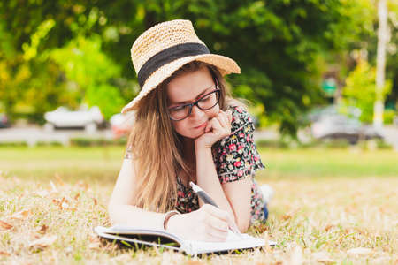 Pretty girl writing a book outside - Attractive person with eyeglasses and straw hat taking notes into her notebook