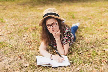 Young woman wearing eyeglasses and a straw hat studying outside while holding a book Pretty girl with brown hair wearing a floral shirt thinking and wondering while sitting in the park