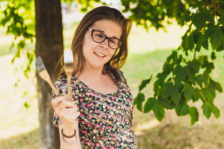 Happy young woman playing with metallic forks outside on a summer day - Pretty girl with eyeglasses having fun and acting silly holding kitchen utensils in the park