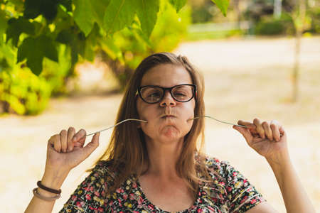 Cute girl having fun playing with a fork outdoors on a sunny day - Pretty young woman with brown hair being funny and acting crazy while sticking kitchen utensil into her cheek in the park