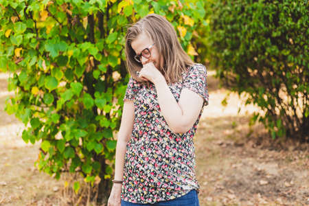 Pretty shy young woman with eyeglasses looking down while standing in nature on a summer day - Casually dressed teen girl with brown hair feeling ashamed and smiling in the park