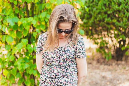 Shy girl standing and looking down - Ashamed woman holding hands behind her back - Nervous teen with sunglasses