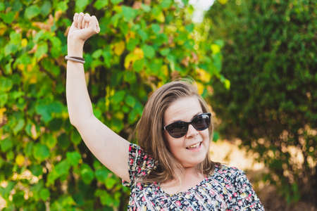 Winner girl holding fist up in the air - Happy successful woman or student wearing sunglasses while being excited