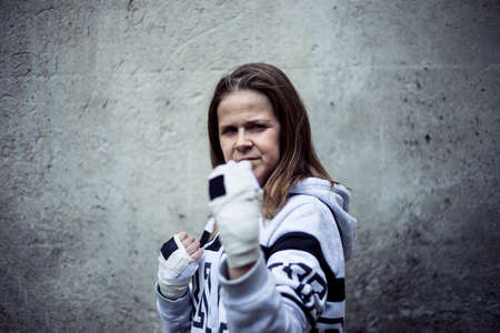 Smiling young female fighter taking defense position in an urban scenery - Strong and confident girl with brown hair wearing white hoodie standing in a black position - Concept image for woman power Foto de archivo