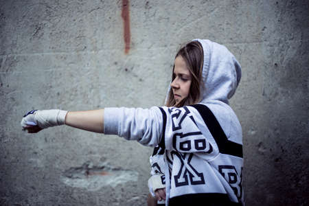 Pretty young woman fighter striking in the air with one hand on an urban background - Cute girl wearing white hoodie punching with one fist in the air outside - Concept image for woman power Foto de archivo