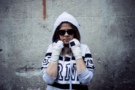 Woman fighter in guard position - Ghetto girl wearing sunglasses ready to fight having a grunge wall behind as background