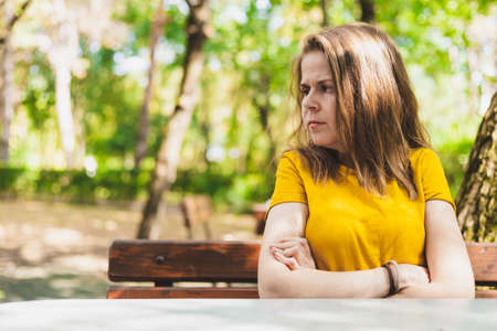 Beautiful young woman sitting with arms crossed on a bench in the park on a summer day - Sad and angry cute teen girl with brown hair looking in the distance outside Banque d'images