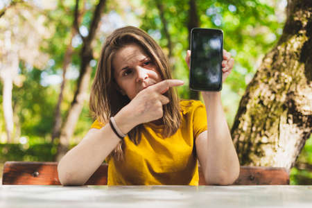 Woman showing phone - Serious girl holding phone - Person pointing with index finger to cellphone blank display