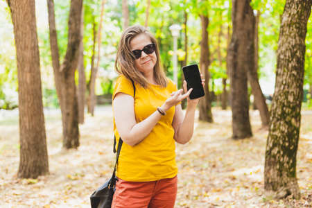 Sad young woman showing to a black mobile phone standing outside on a summer day - Unhappy teen girl wearing sunglasses holding a small gadget in the park - Surprised female with modern technology