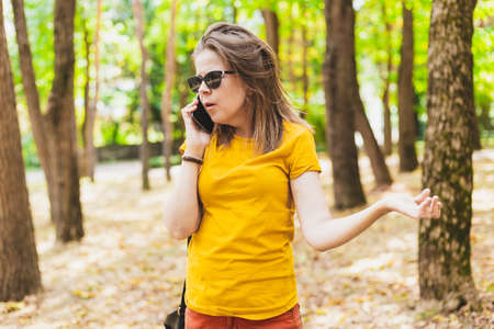 Beautiful young woman talking on the mobile phone in the park - Angry teen girl wearing sunglasses receiving an unknown call - Surprised sad female holding a telephone while walking outside