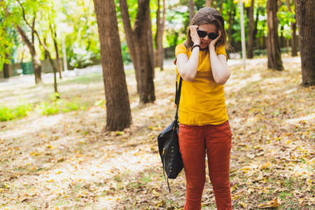 Woman with headache - Girl having a migraine outside in nature while wearing sunglasses - Young person massage herself to relief head pain Foto de archivo