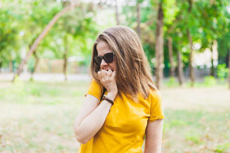 Nervous woman biting nails - Anxious girl with sunglasses and yellow t shirt having an addiction of nibbling fingernail Banque d'images