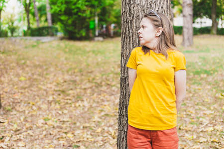 Beautiful young woman hiding scared behind a tree in the park on a summer day - Casually dressed teen girl with brown hair suffering from anxiety while sitting alone in nature - Having a panic attack