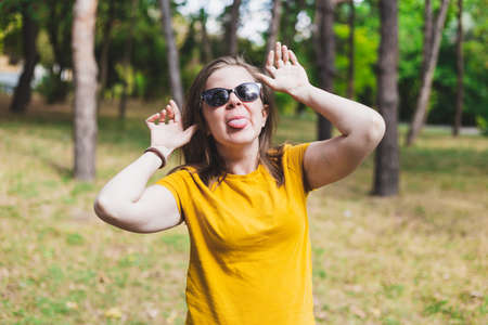Woman with funny face - Girl grimacing outside while wearing sunglasses and a vibrant yellow shirt - Person doing silly monkey expression