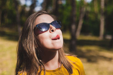 Pretty girl sticking out tongue - Funny and playful woman grimacing in the sunlight in the forest enjoying summer