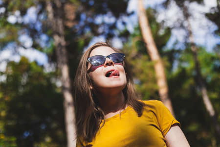 Beautiful young woman showing tongue while acting silly in the park - Happy cute teen girl sticking her tongue out pointing up - Casually dressed female with brown hair and wearing sunglasses relaxing