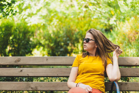 Beautiful woman fixing her hair while sitting on a bench in the park - Attractive girl wearing sunglasses playing with her hair in nature - Casually dressed teen female standing and looking away Foto de archivo