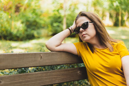 Thoughtful woman sitting on a bench - Girl daydreaming in public while wearing sunglasses and a yellow t shirt