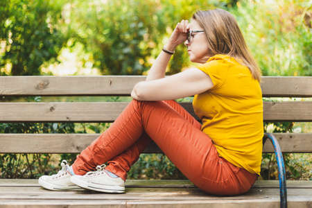 Woman sitting on bench and thinking - Thoughtful student in fetus position searching for a solution to her problems Banque d'images