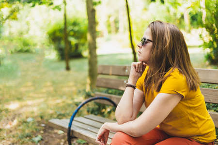 Thinking woman looking forward - Thoughtful girl sitting on bench - Lonely girl - Teenager waiting outside while daydreaming Foto de archivo