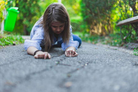 Young woman suffering from epilepsy felt on the ground outside on a summer day - Sick pretty girl lying on rough concrete after a seizure - Female worker fainted from stress and exhaustion