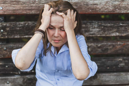 Panic attack while sitting on a bench - Woman suffering from anxiety disorder - Scared girl holding her hands on the head