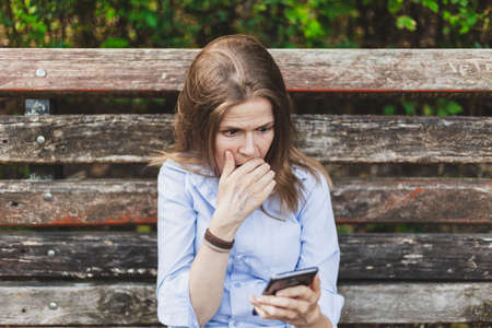 Beautiful young woman looking scared and surprised while sitting on a bench in the park on a summer day - Pretty girl with brown hair wearing a casual outfit standing alone while having a panic attack outdoors