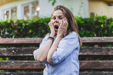 Beautiful young woman feeling scared and anxious while holding her face with both hands outside - Pretty girl suffering from depression standing alone in the park - Stressed female worker having a panic attack